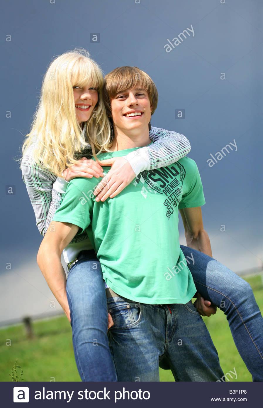 young man outdoors piggybacking woman and smiling Stock Photo