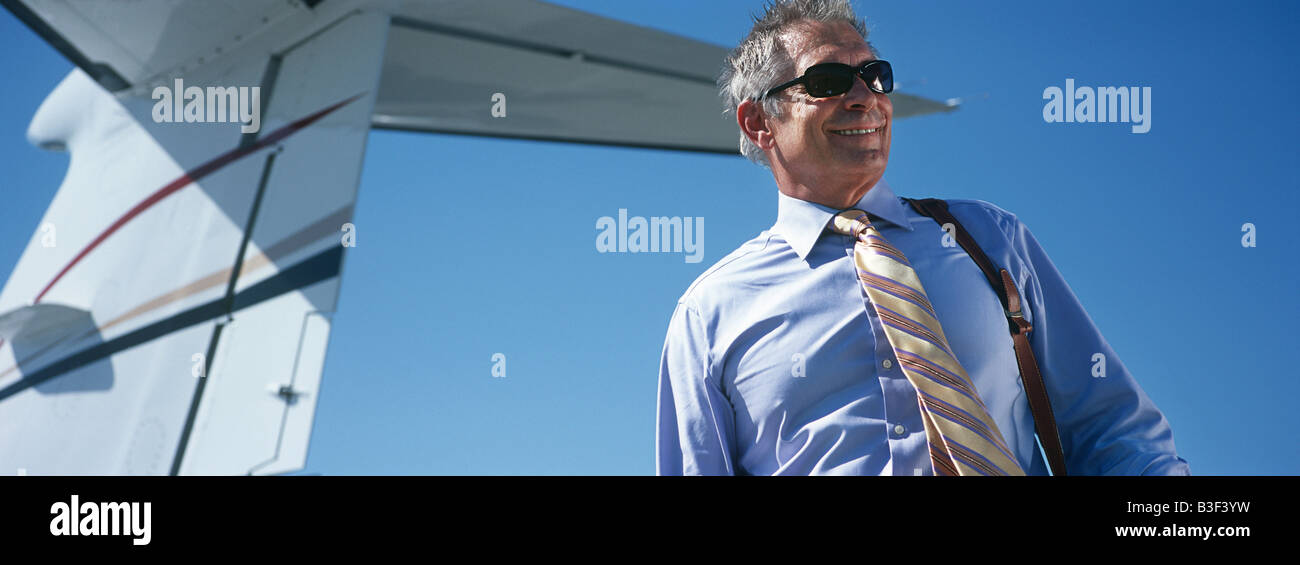 Business man by tail of private plane - Stock Image