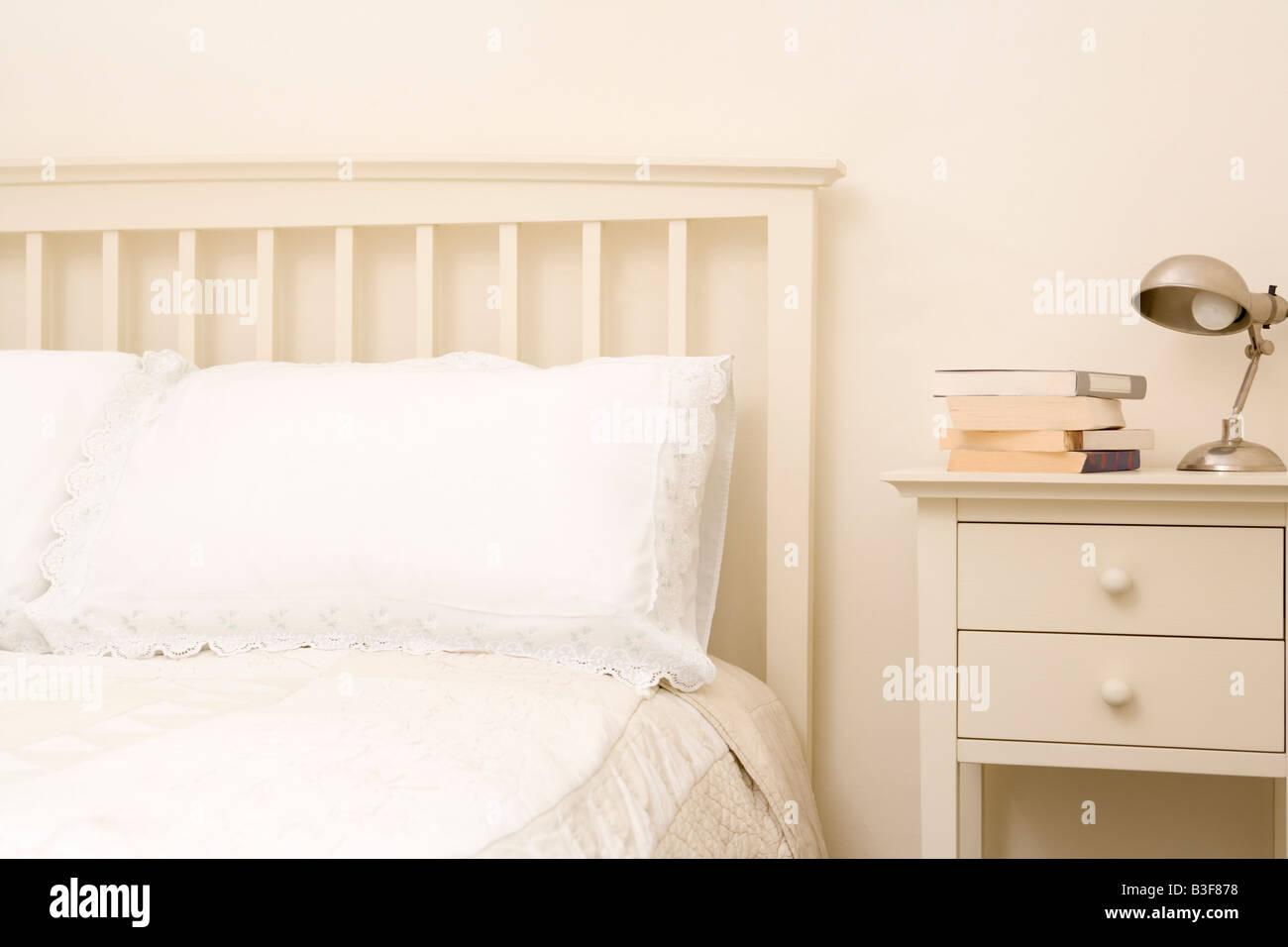 Empty bedroom with books on nightstand - Stock Image