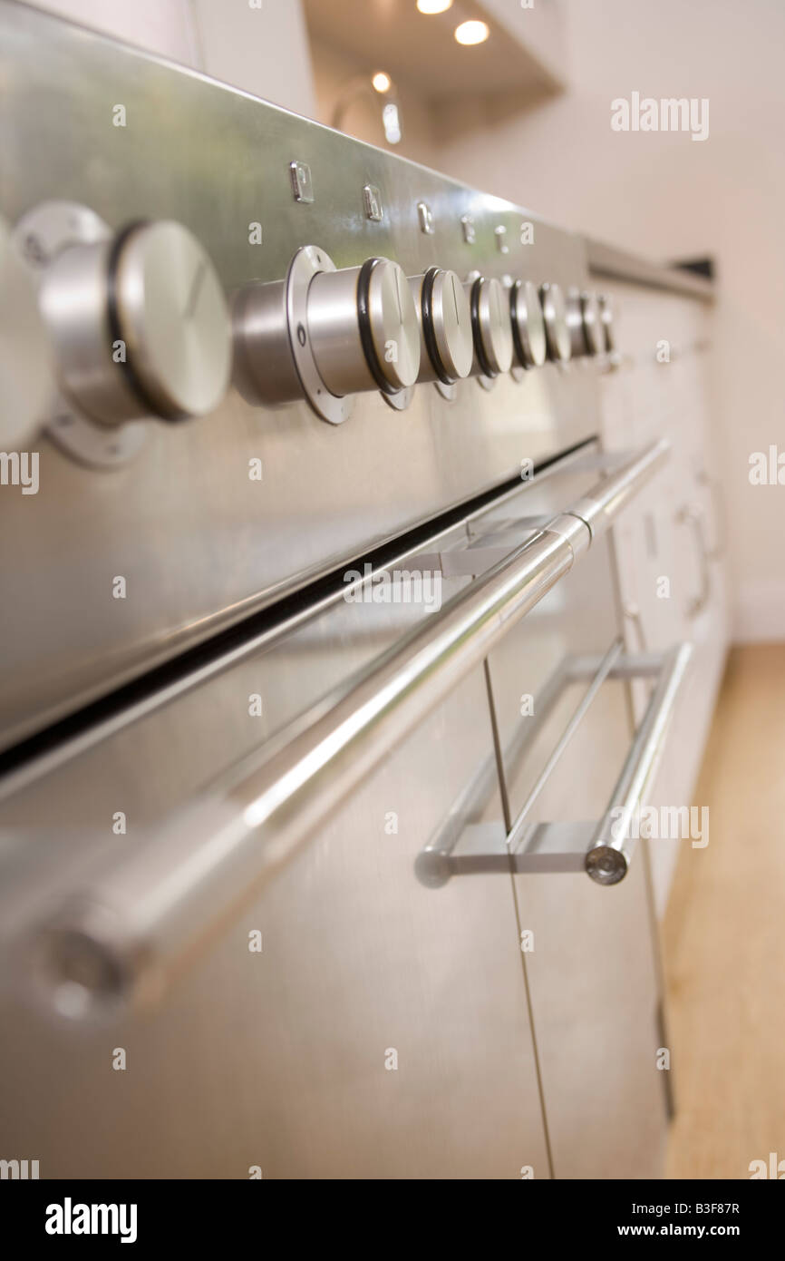 Empty kitchen with focus on stove dials - Stock Image