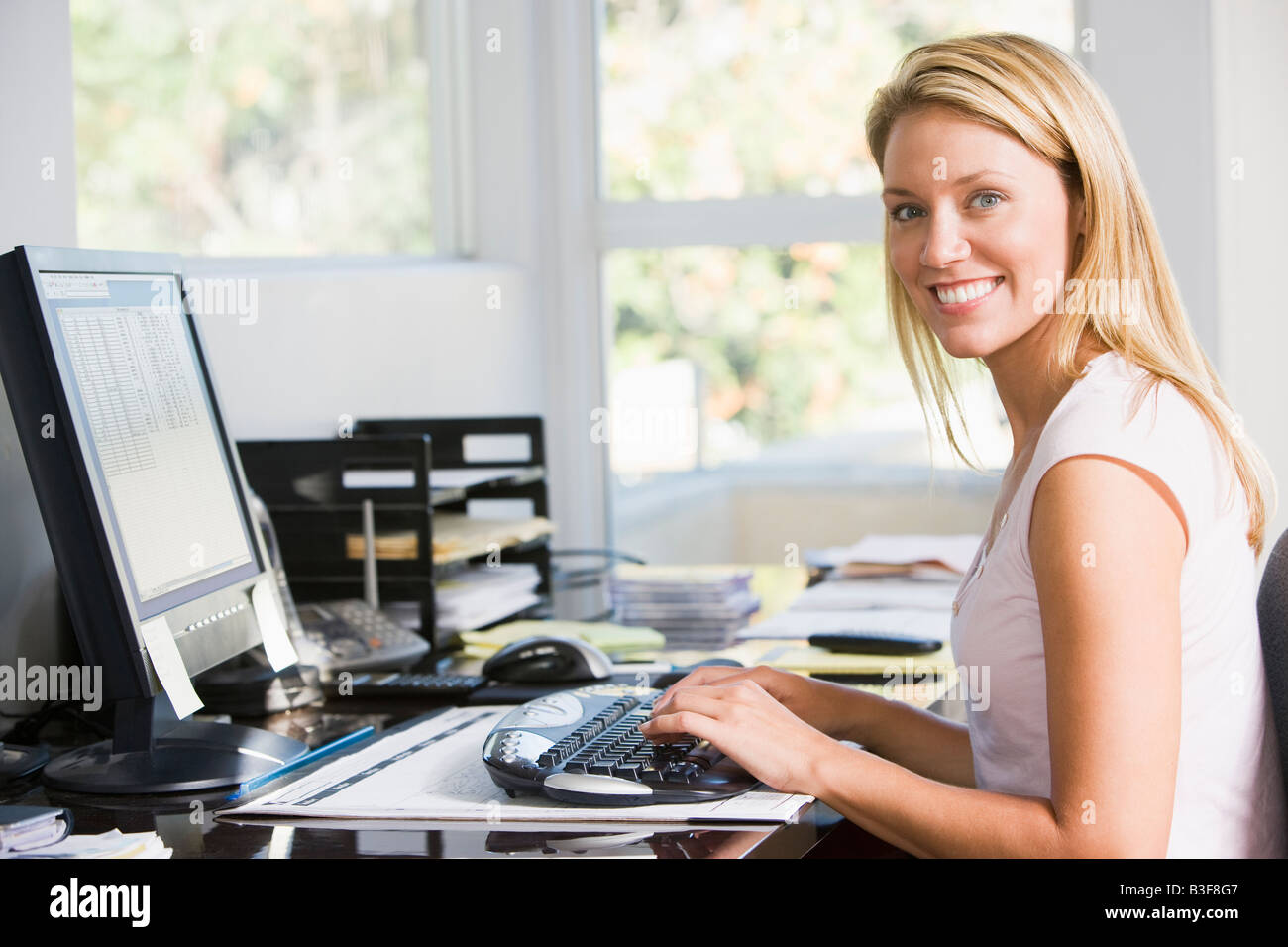 Woman in home office with computer smiling - Stock Image