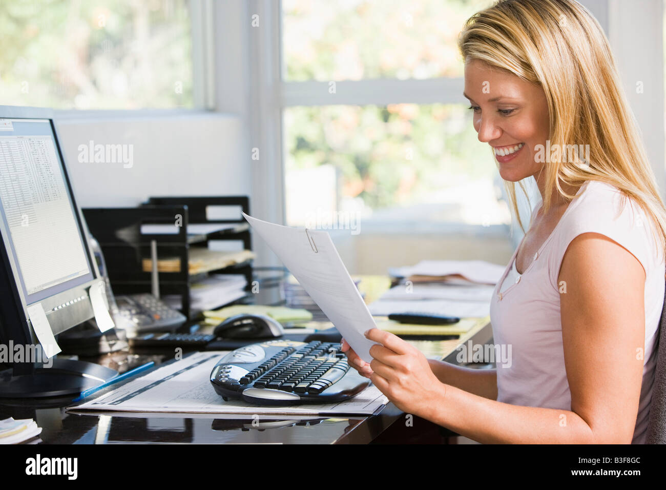 Woman in home office with computer and paperwork smiling - Stock Image