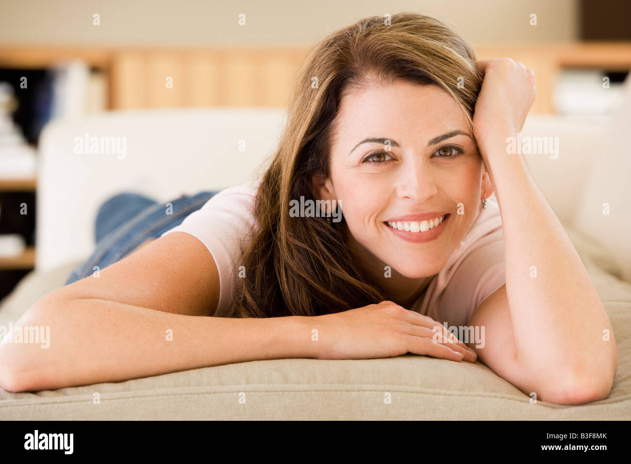 Woman lying in living room - Stock Image
