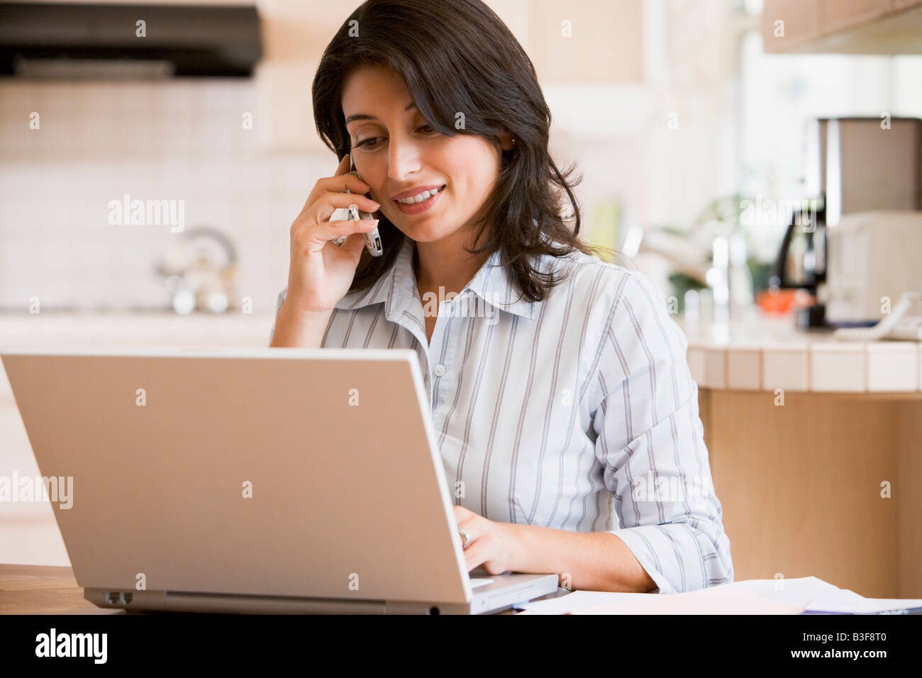 Woman in kitchen with laptop using cellular phone smiling - Stock Image