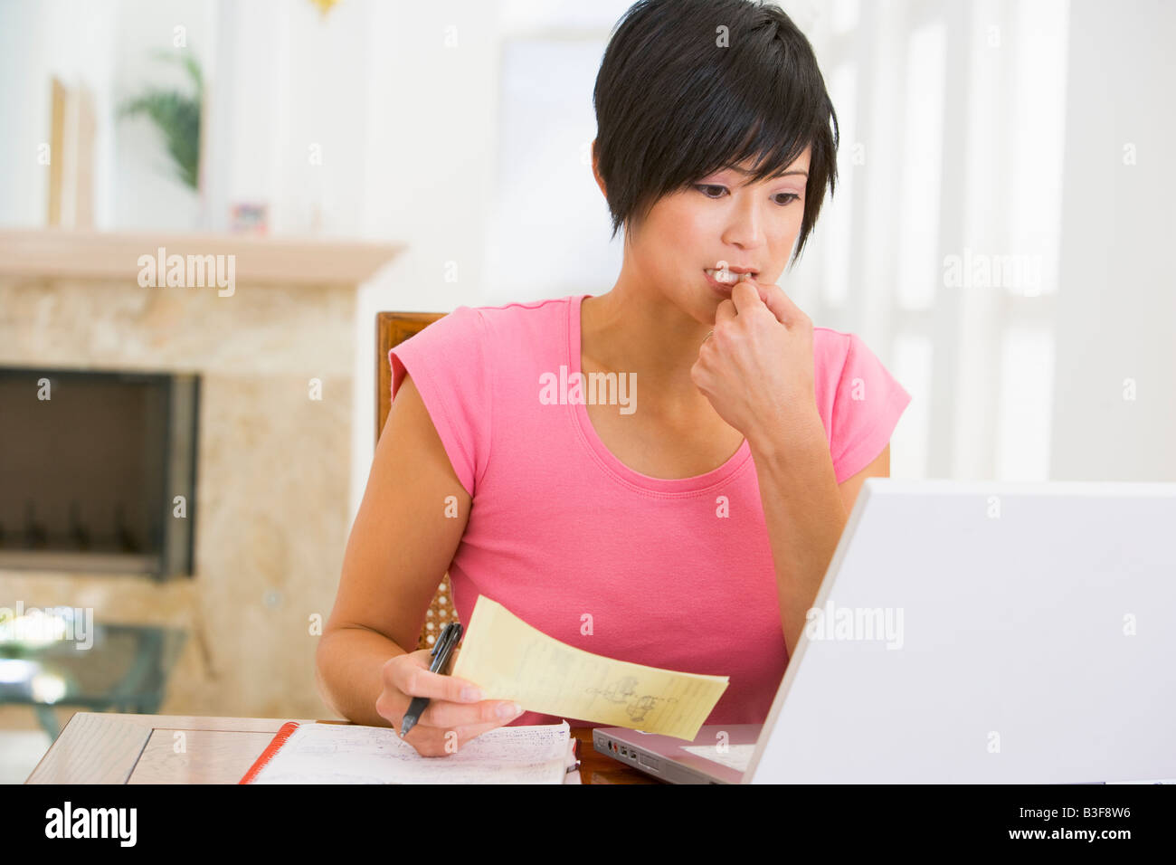 Woman in dining room with laptop thinking - Stock Image