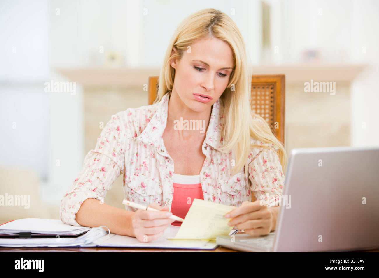 Woman in dining room with laptop smiling - Stock Image