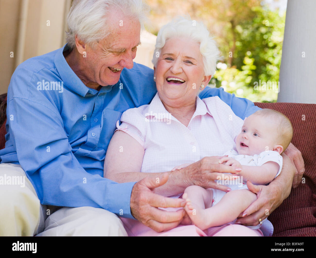 Grandparents outdoors on patio with baby smiling - Stock Image