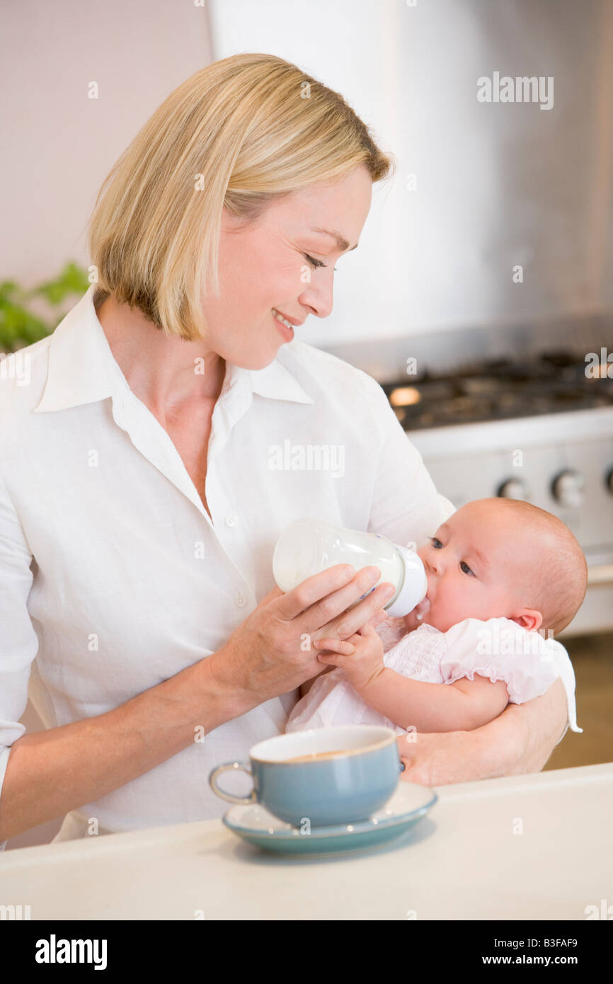 Mother feeding baby in kitchen with coffee smiling - Stock Image