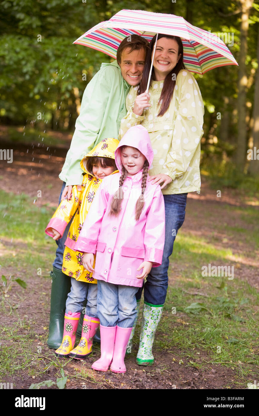Family outdoors in rain with umbrella smiling - Stock Image