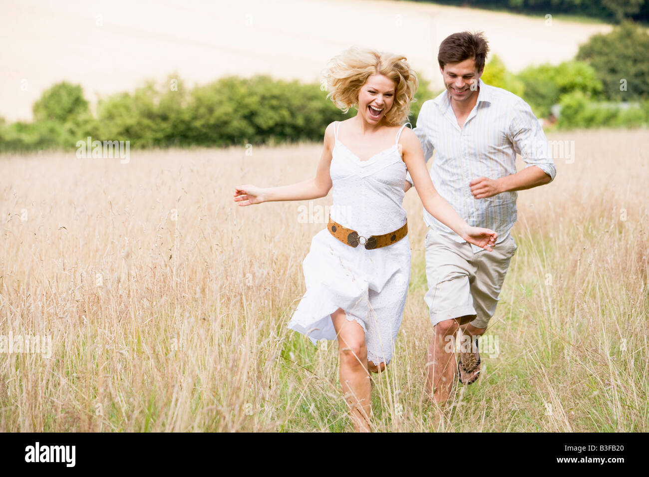 Couple running outdoors smiling - Stock Image