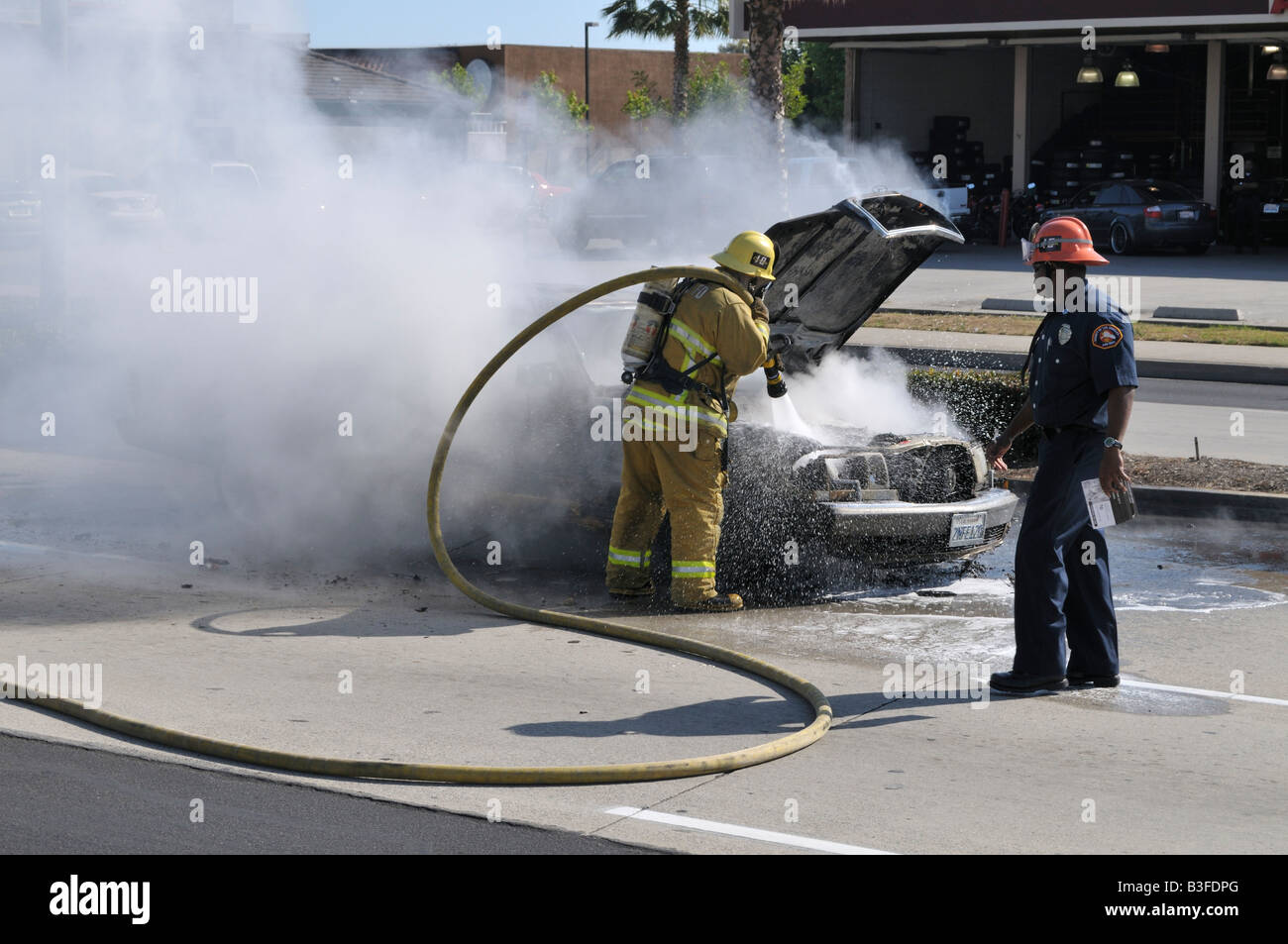 Firefighter Putting Out Fire On Burning Mercedes   Stock Image