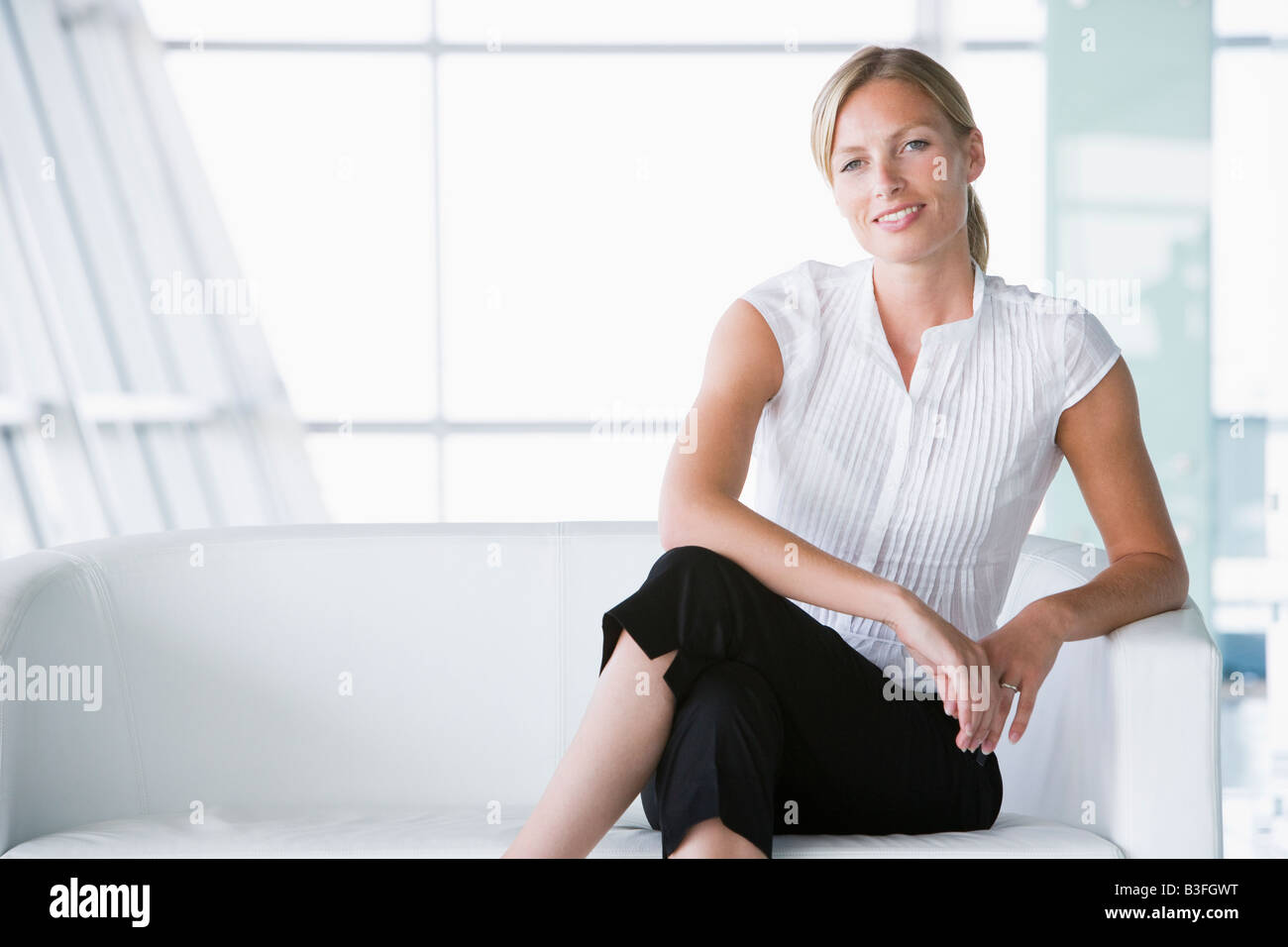 Businesswoman sitting in office lobby smiling - Stock Image