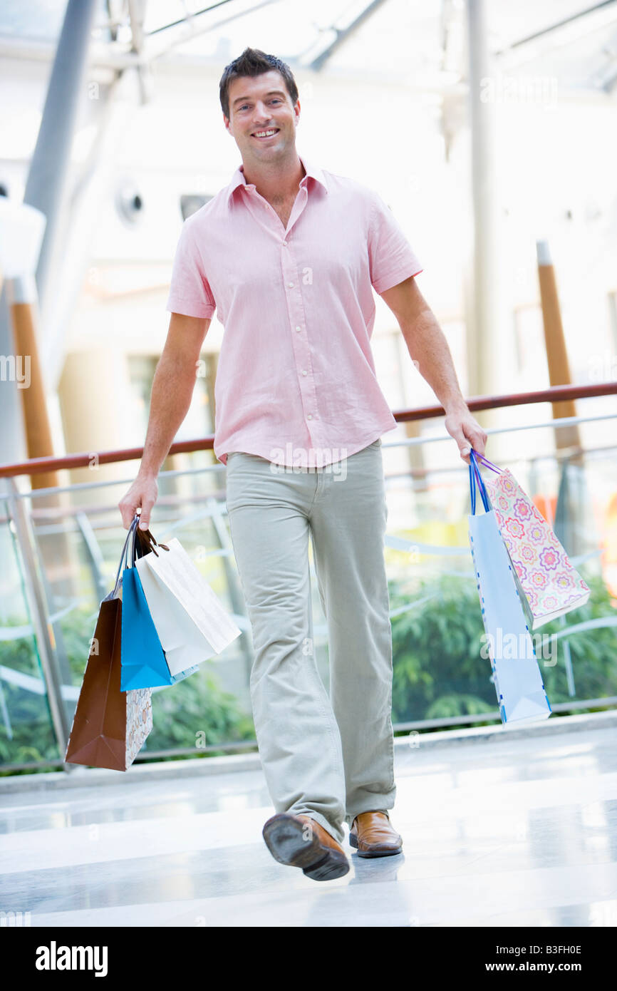 Man with shopping bags at a shopping mall - Stock Image