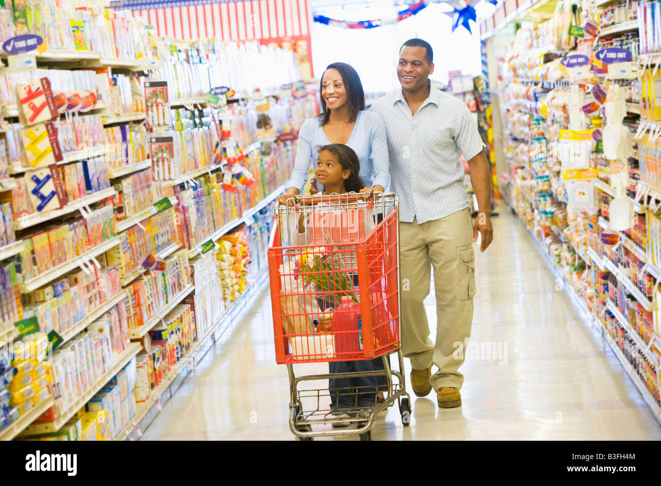 Mother and father with young daughter shopping at the grocery store. - Stock Image