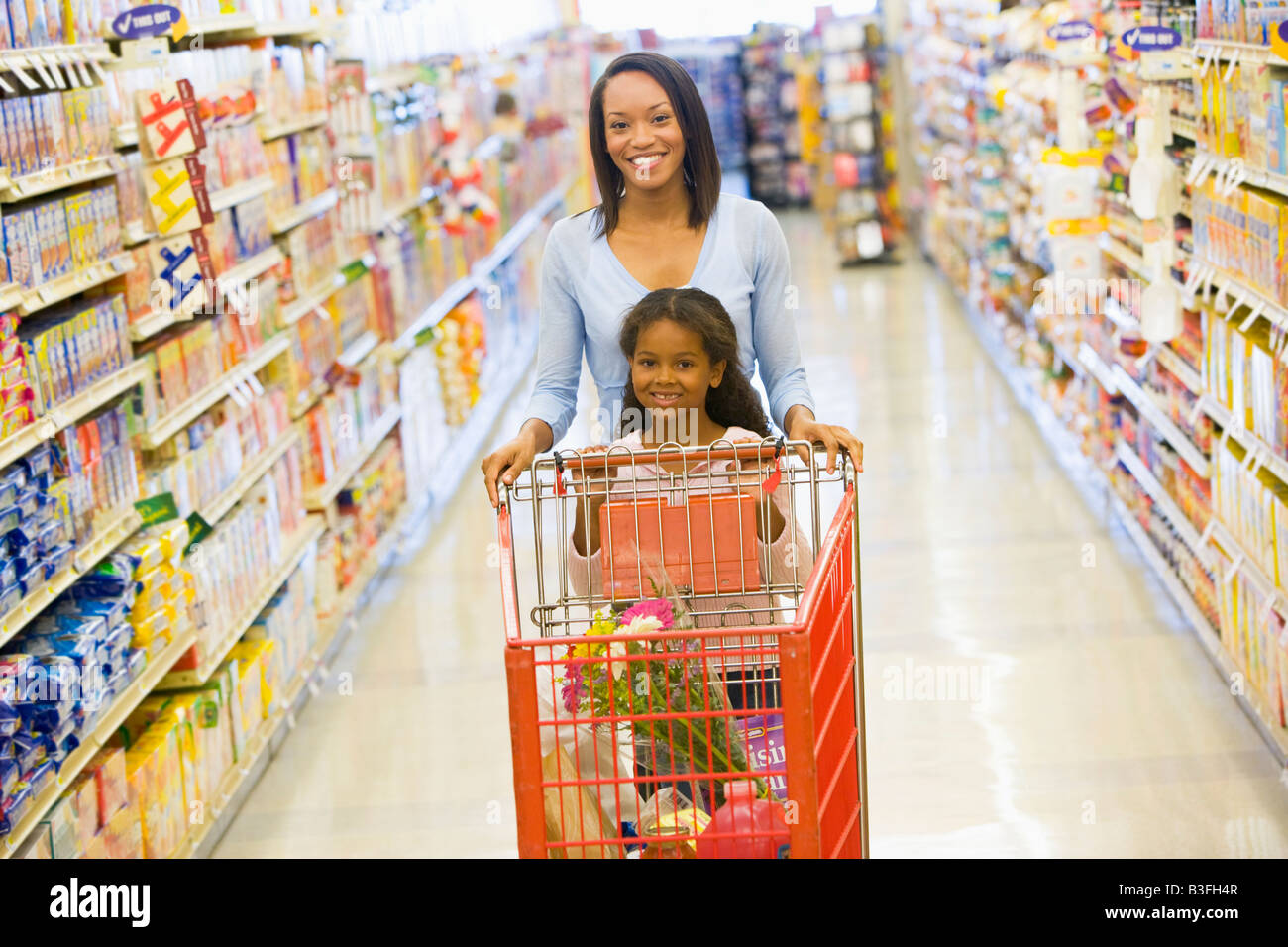 Mother with young daughter shopping at the grocery store. - Stock Image