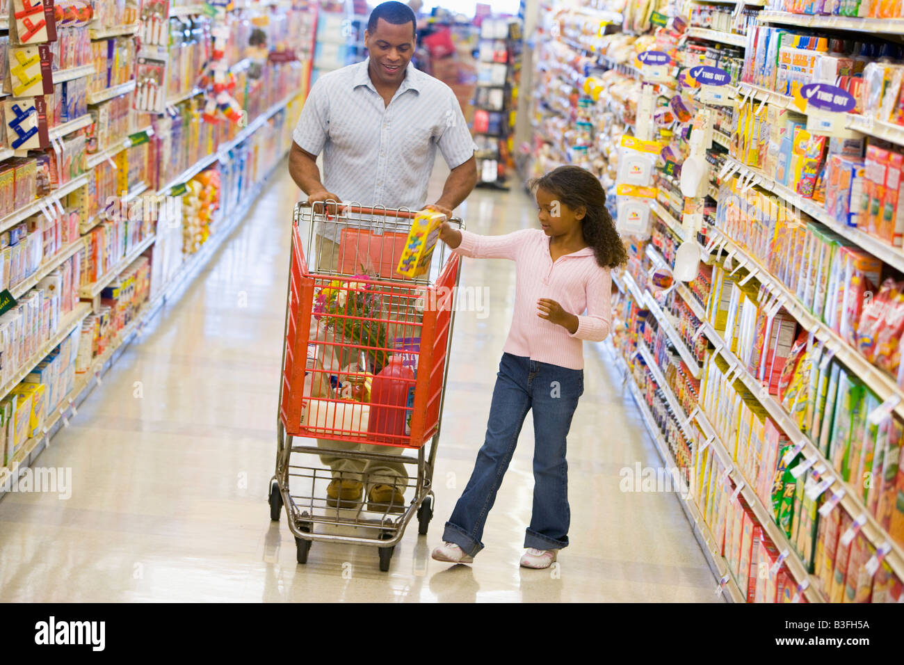 Father and daughter shopping at a grocery store - Stock Image