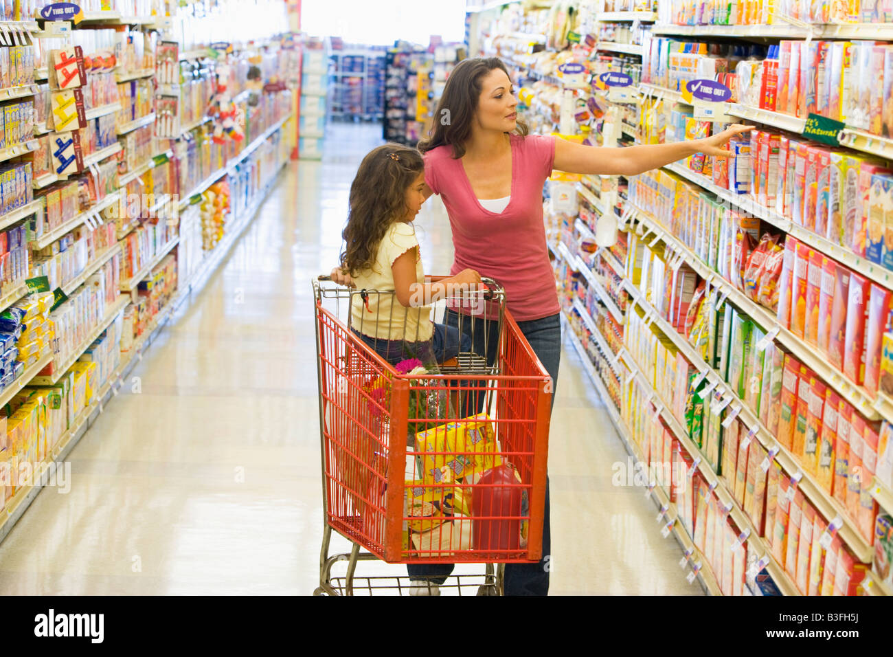 Mother and young daughter shopping at a grocery store - Stock Image