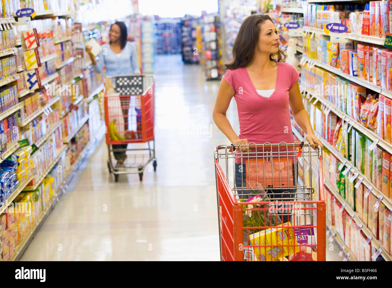 Two women shopping at a grocery store - Stock Image