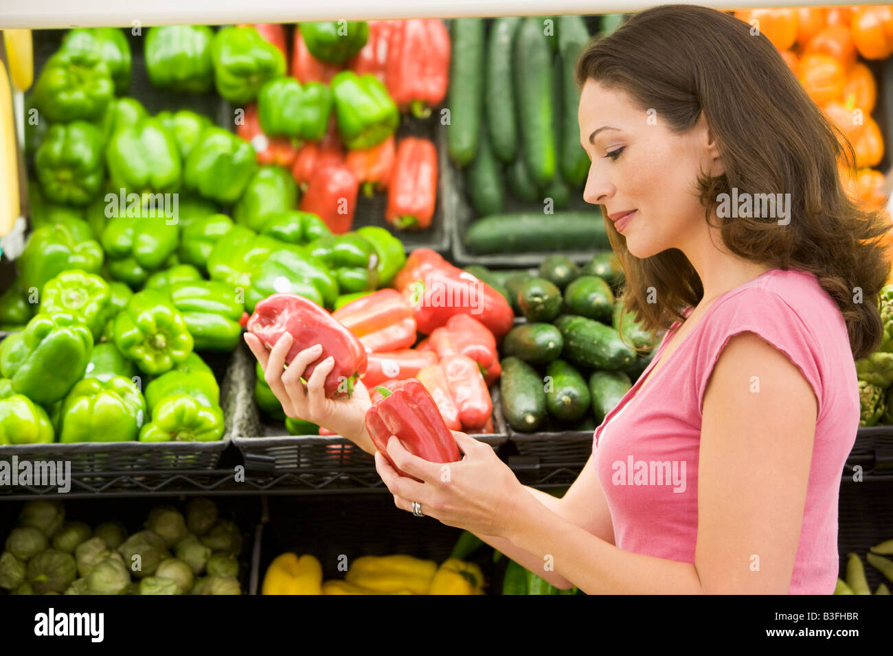 Woman shopping for bell peppers at a grocery store - Stock Image