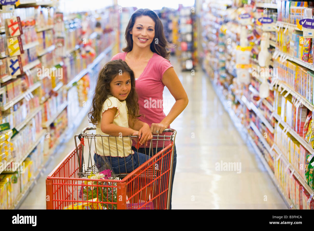 Mother and young daughter shopping at a grocery store. - Stock Image