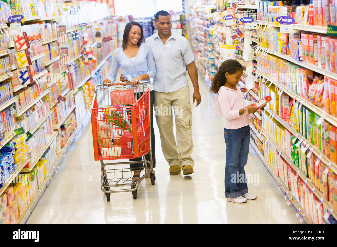 Mother and father with young daughter shopping at a grocery store. - Stock Image