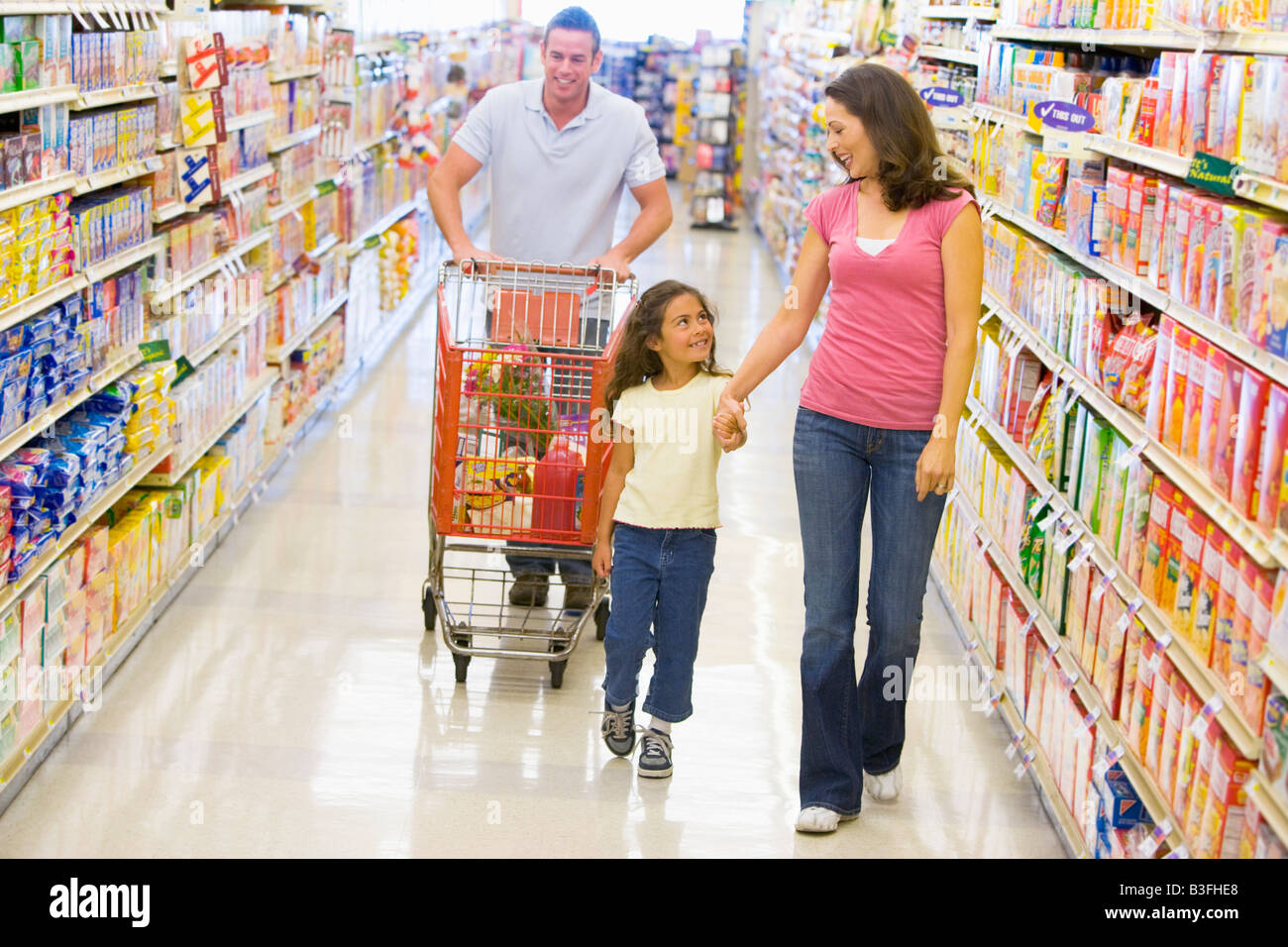 Mother and father with young daughter shopping for a new car - Stock Image