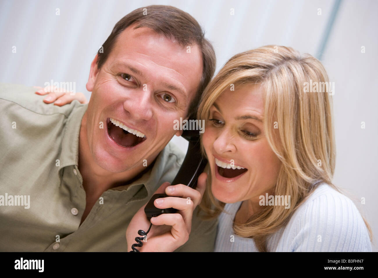 Couple receiving a good news phone call from clinic - Stock Image