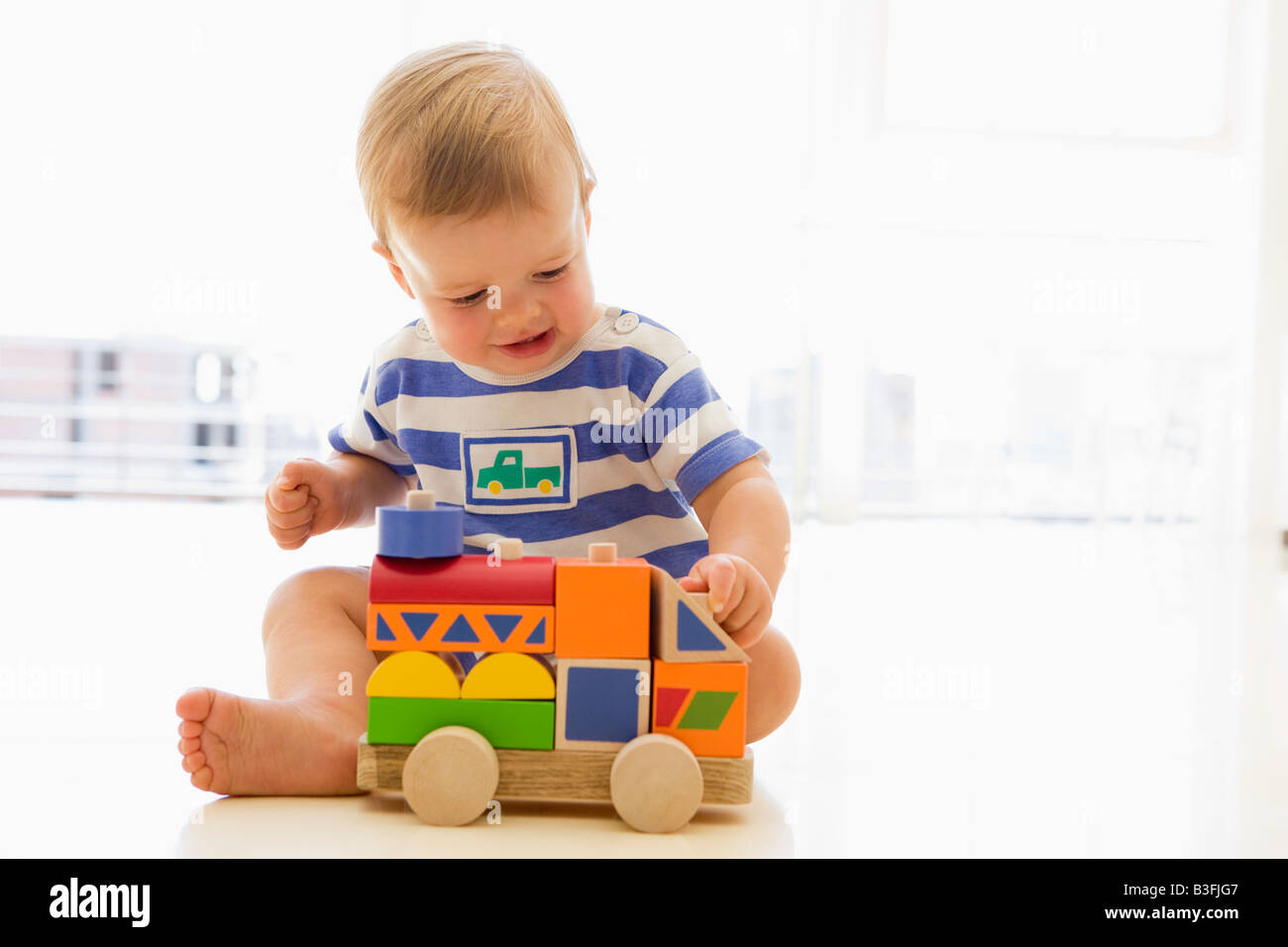 Baby indoors playing with truck - Stock Image
