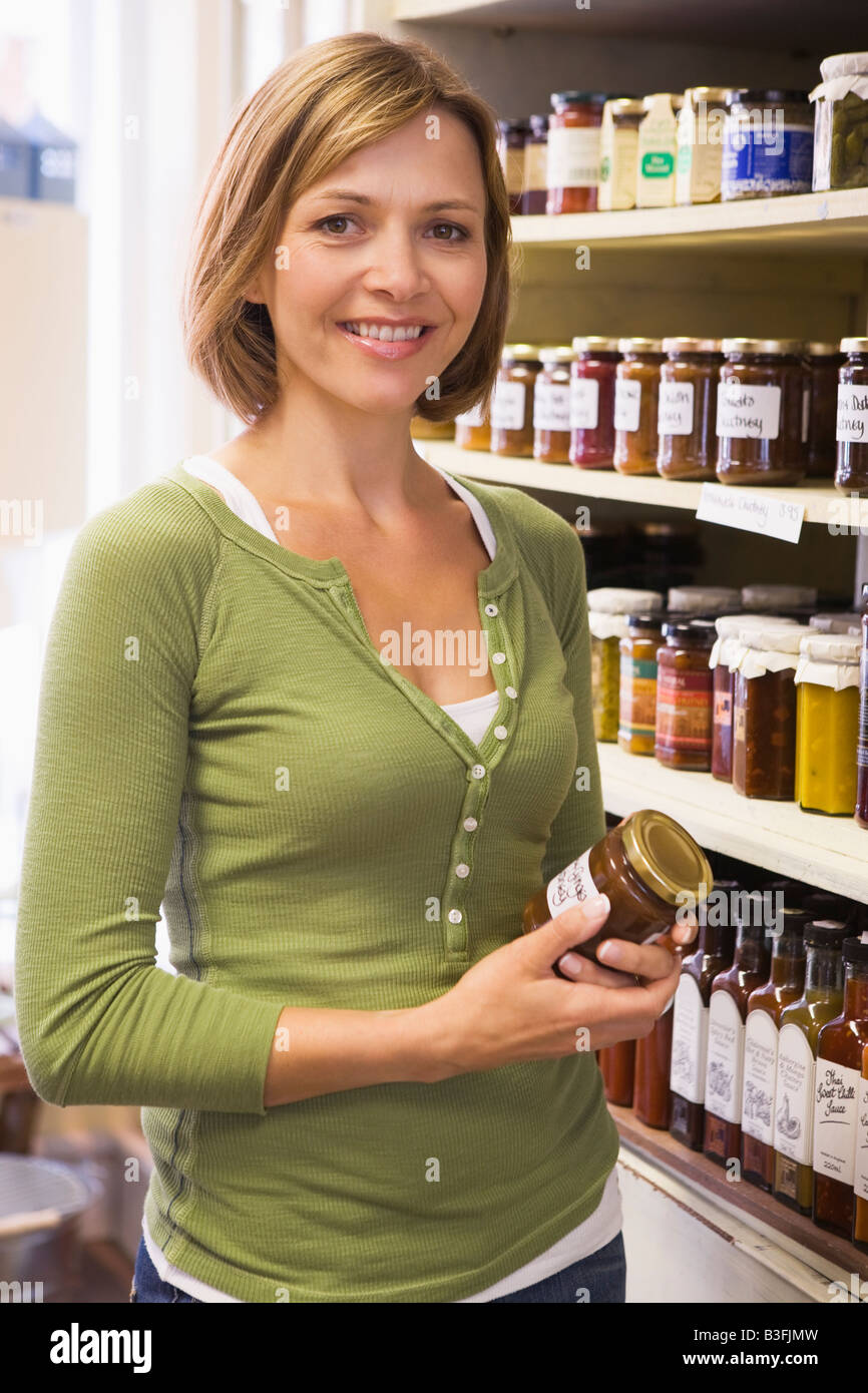 Woman in market looking at preserves smilingStock Photo