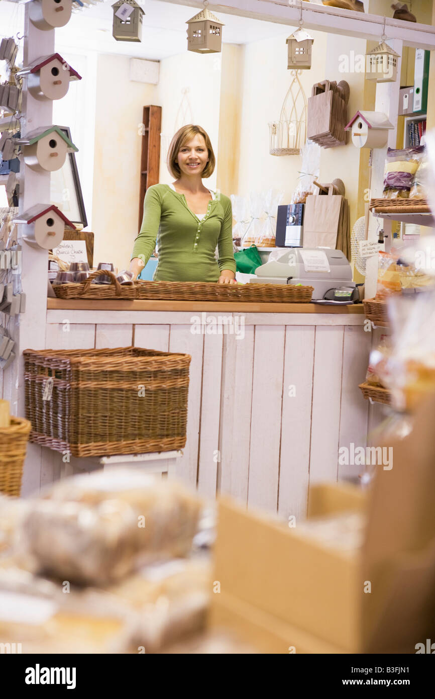 Woman in birdhouse store smiling - Stock Image