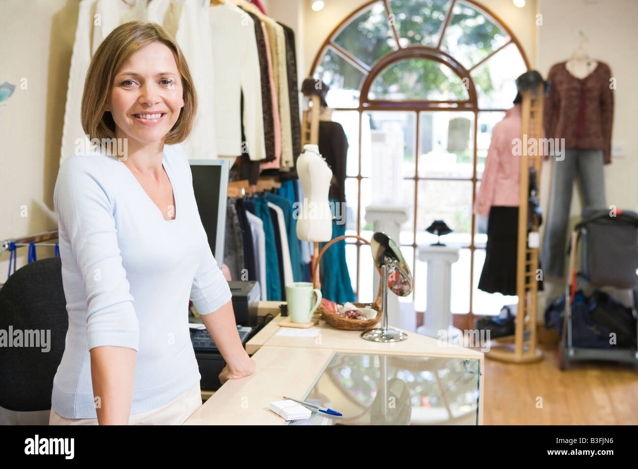 Woman at clothing store smiling - Stock Image