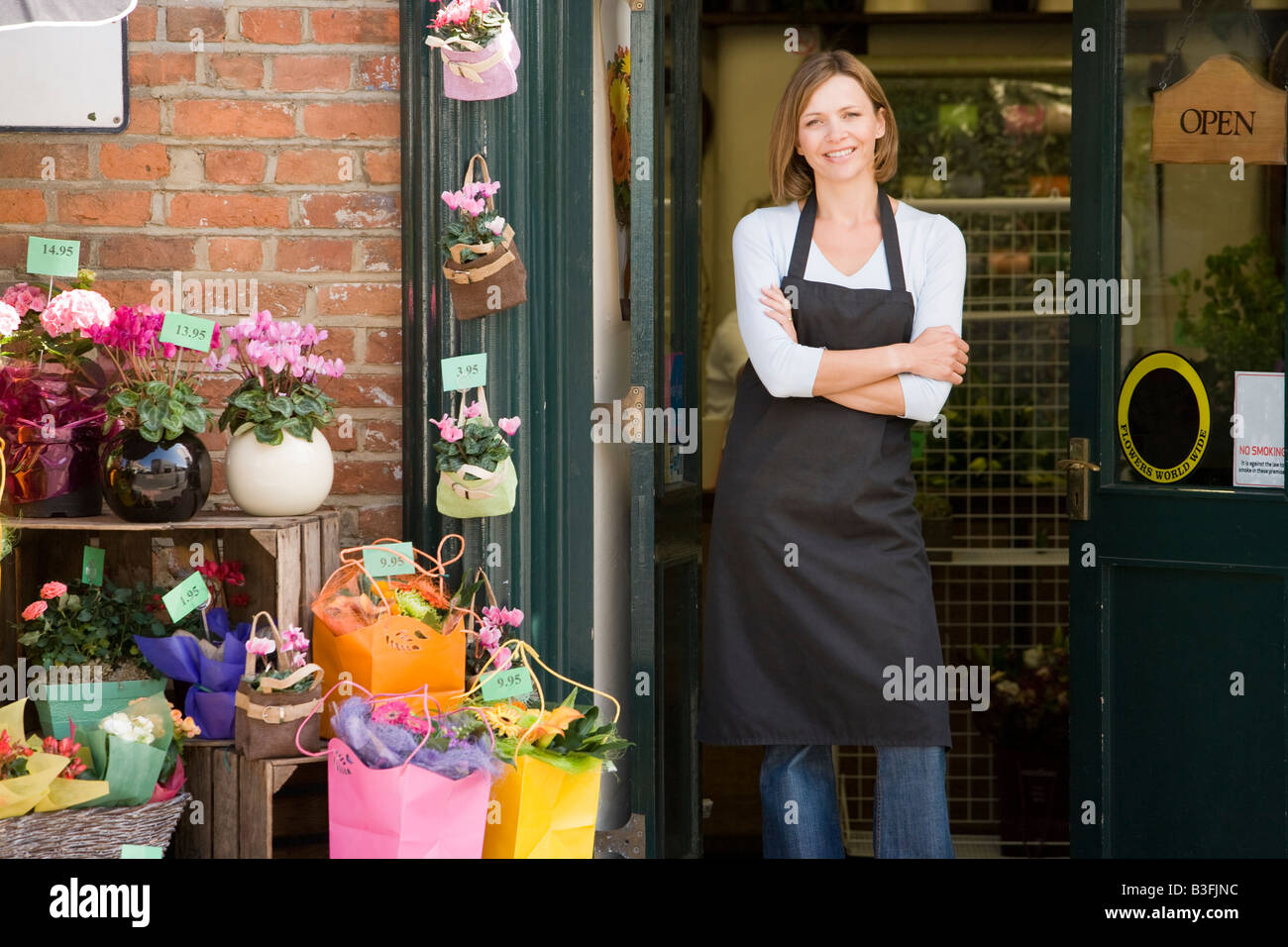 Woman working at flower shop smiling - Stock Image