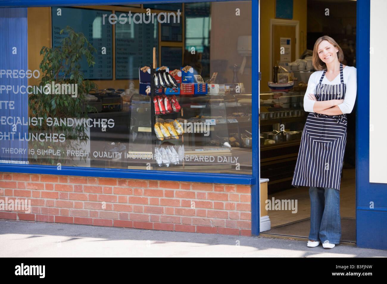 Woman standing in doorway of restaurant smiling - Stock Image