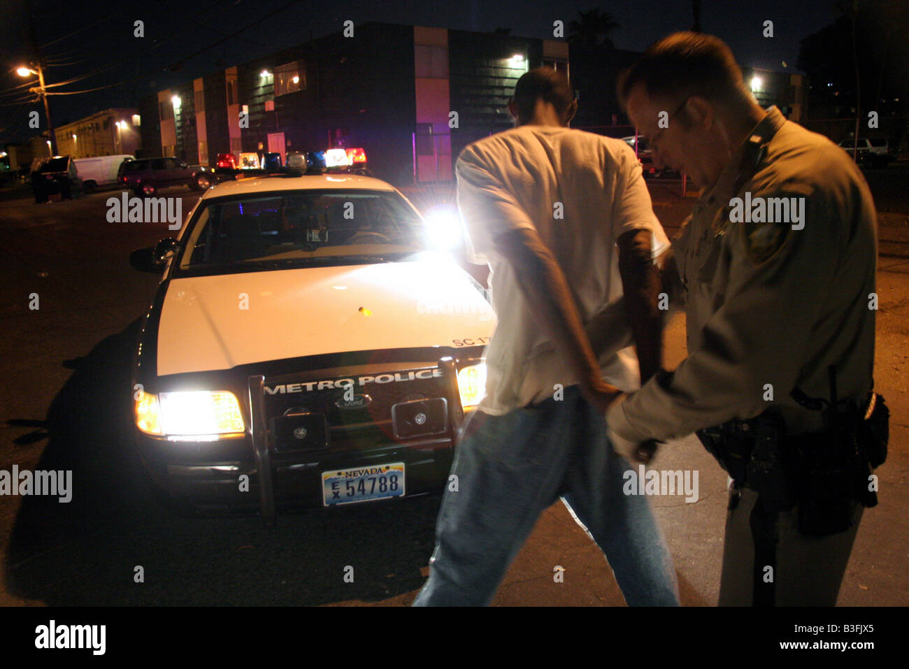 Las Vegas Police Officer searching a suspect in a back street at night - Stock Image