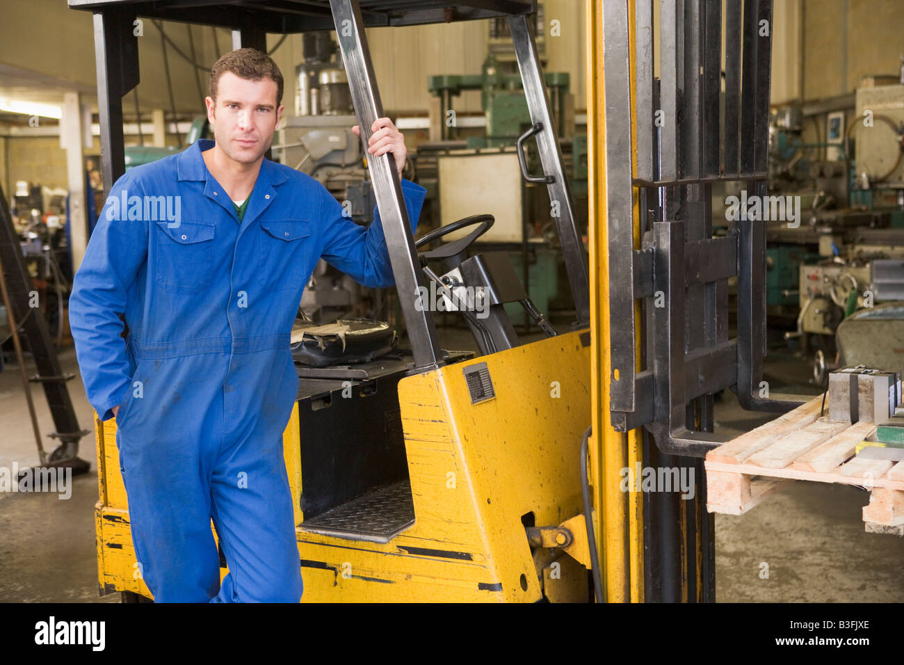 Warehouse worker standing by forklift - Stock Image