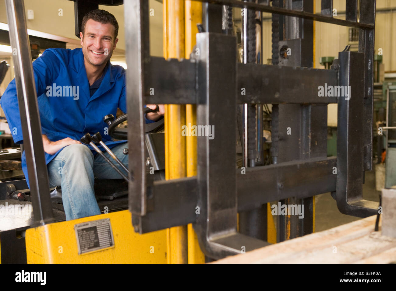 Warehouse worker in forklift - Stock Image