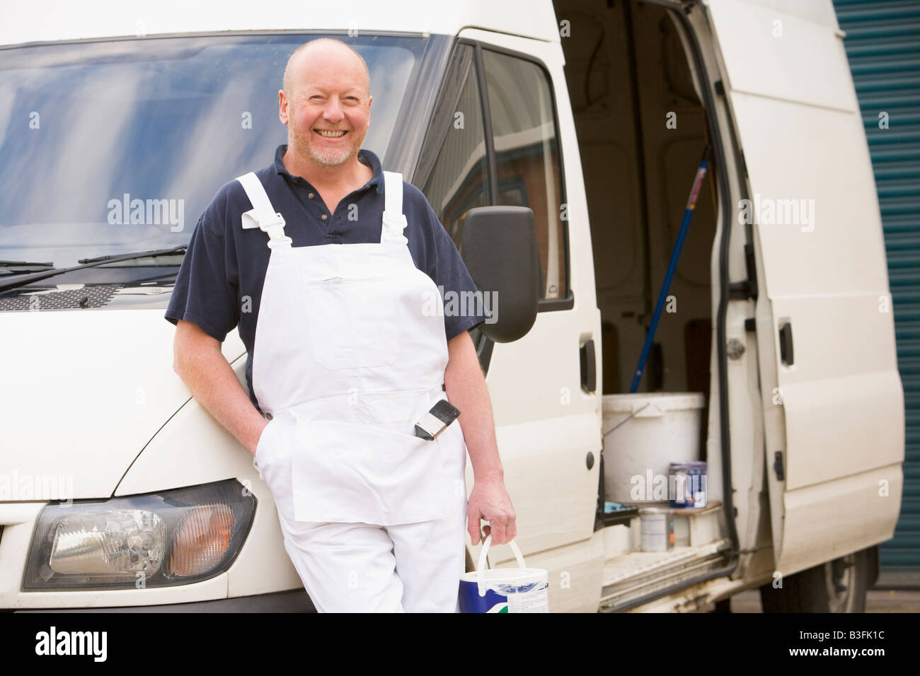 Painter standing with van smiling - Stock Image