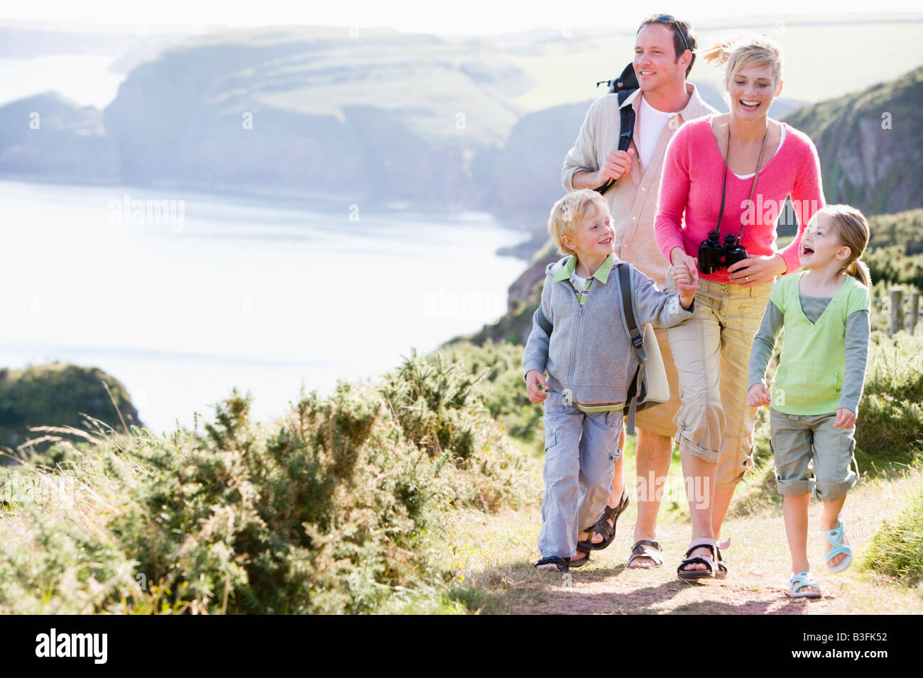 Family walking on cliffside path holding hands and smiling - Stock Image