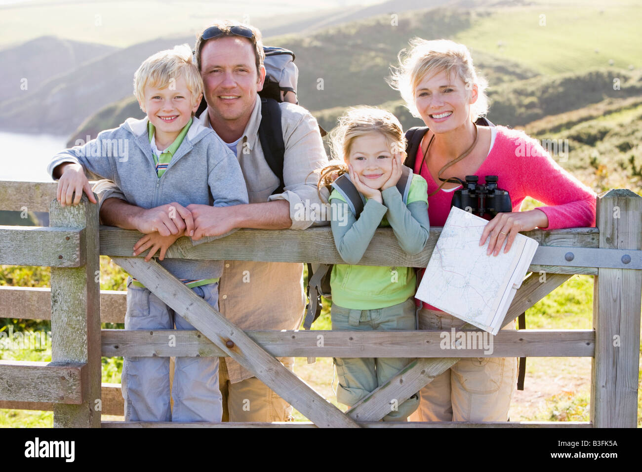 Family on cliffside path leaning on fence and smiling - Stock Image