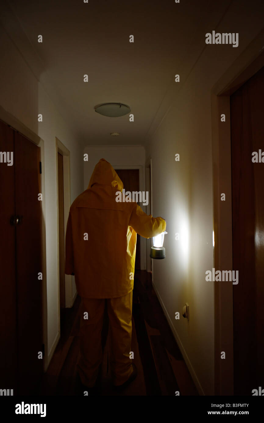 Man in corridor with lantern wearing wet weather gear - Stock Image