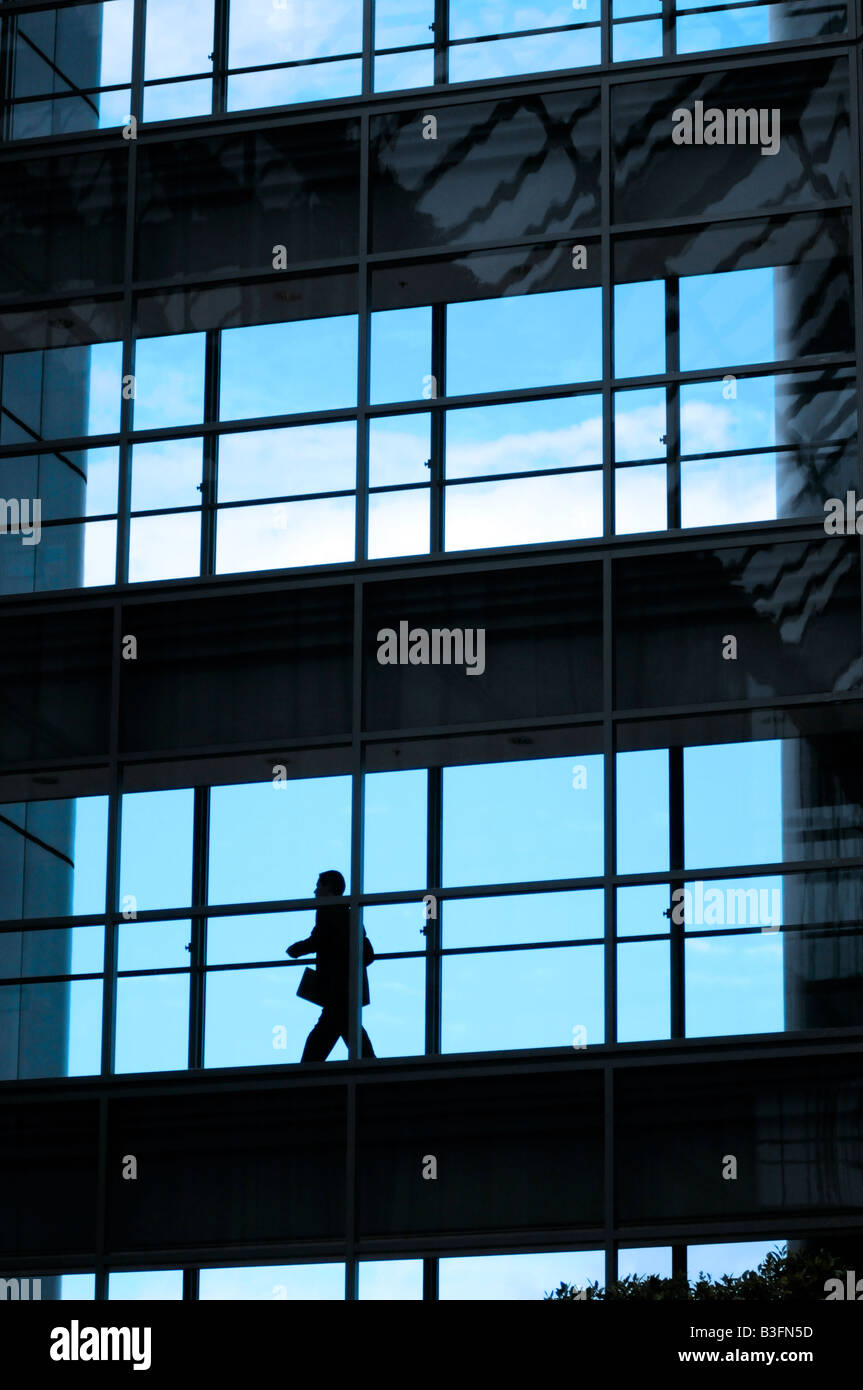 Royalty free photograph of business man walking in glass office building silhouetted against the evening sky. - Stock Image