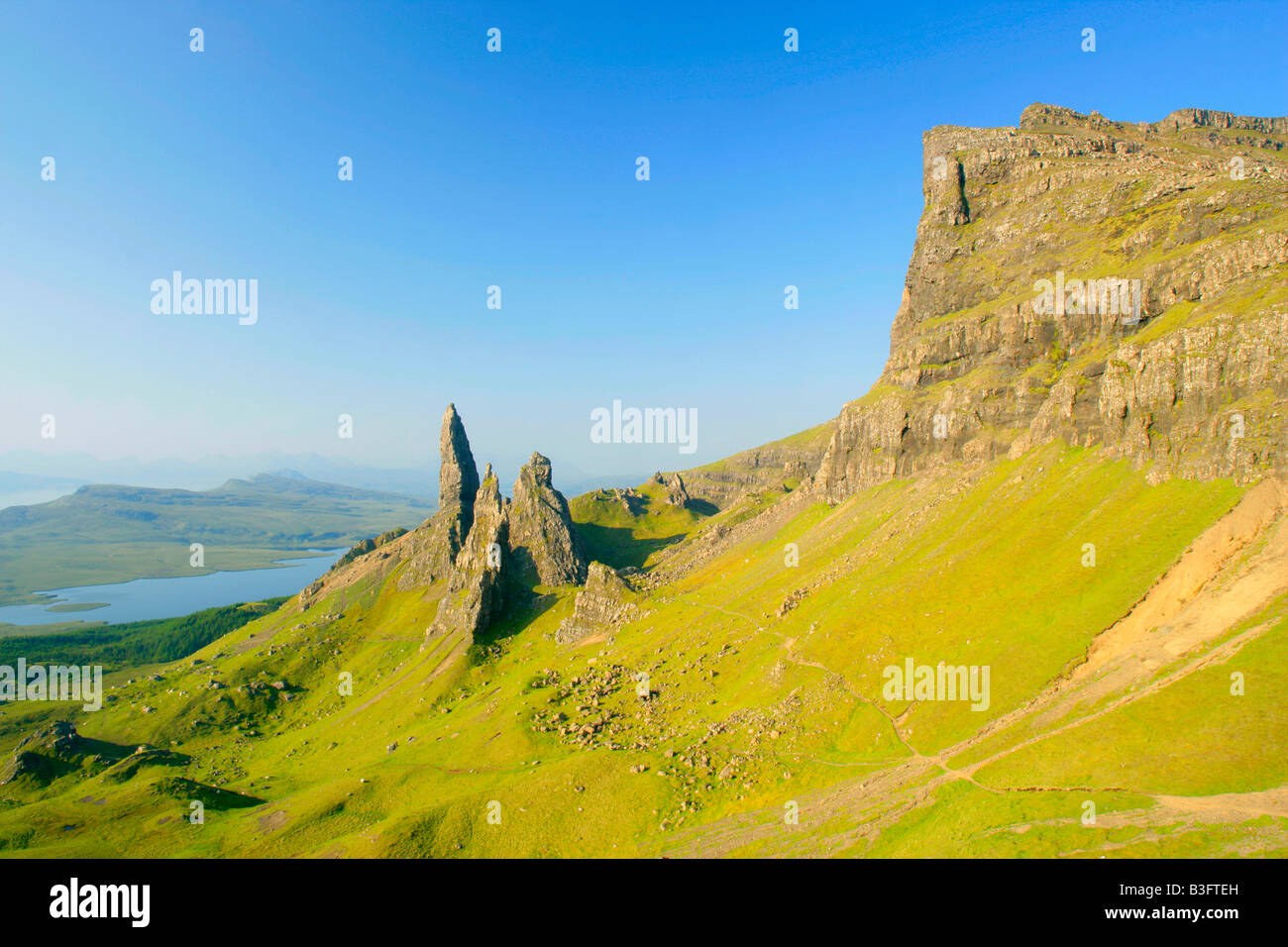 Mountain scenery rolling green slopes cliffs of The Storr and bizarre rock formation Old Man of Storr seen from Stock Photo