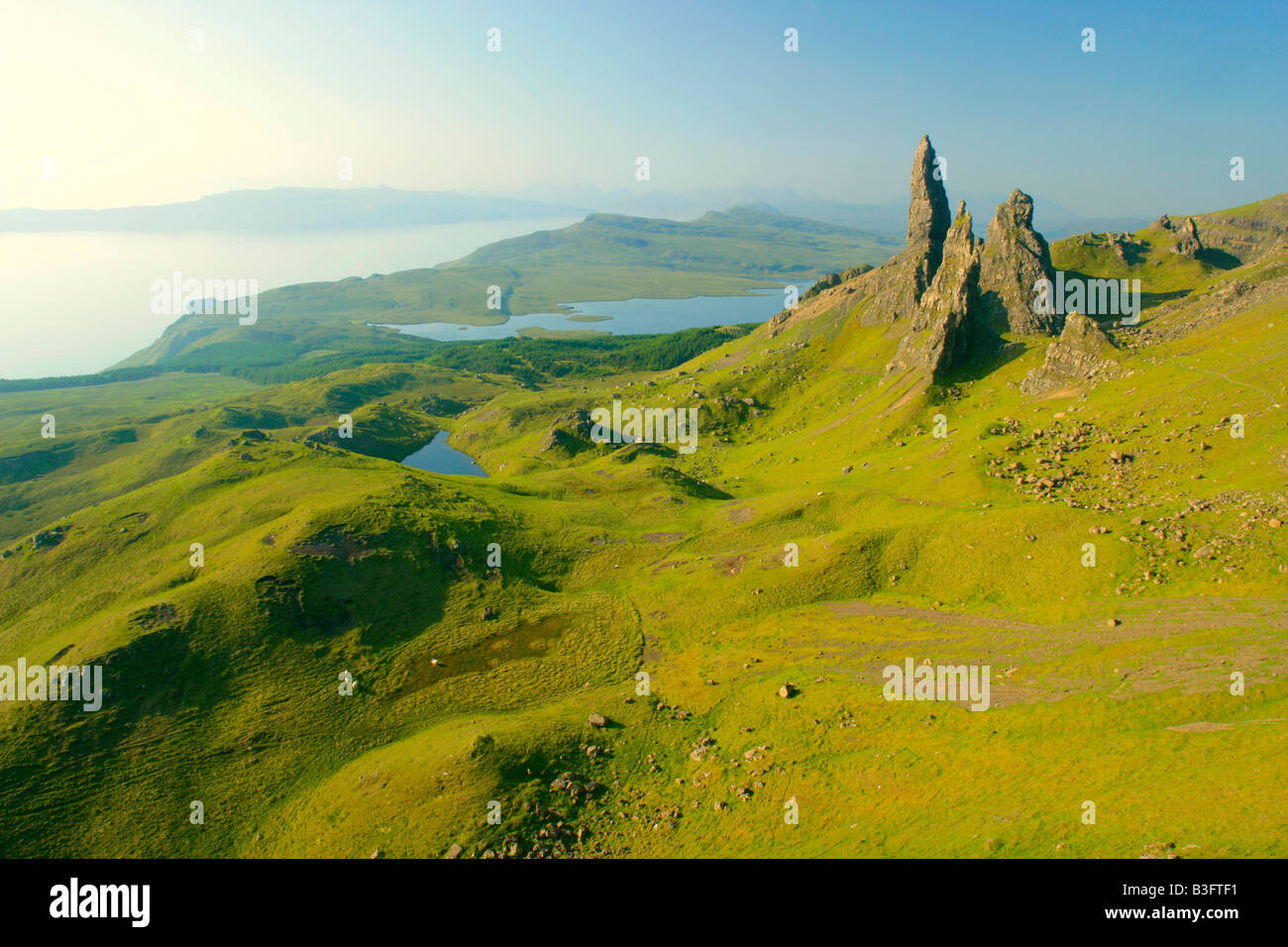 Mountain scenery rolling green slopes and bizarre rock formation Old Man of Storr seen from above Stock Photo