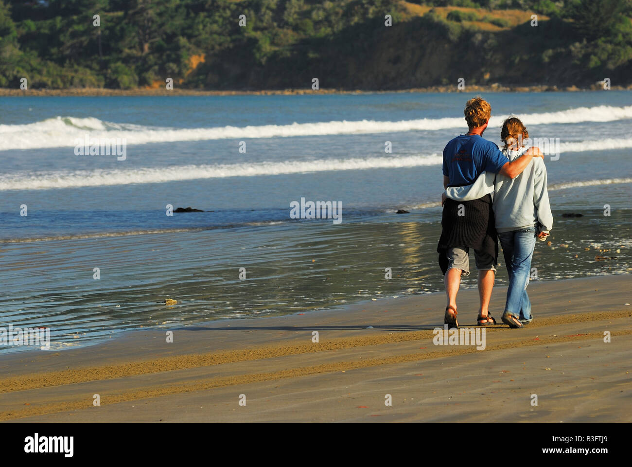 young pair walking on the beach - pacific ocean new zealand - Stock Image