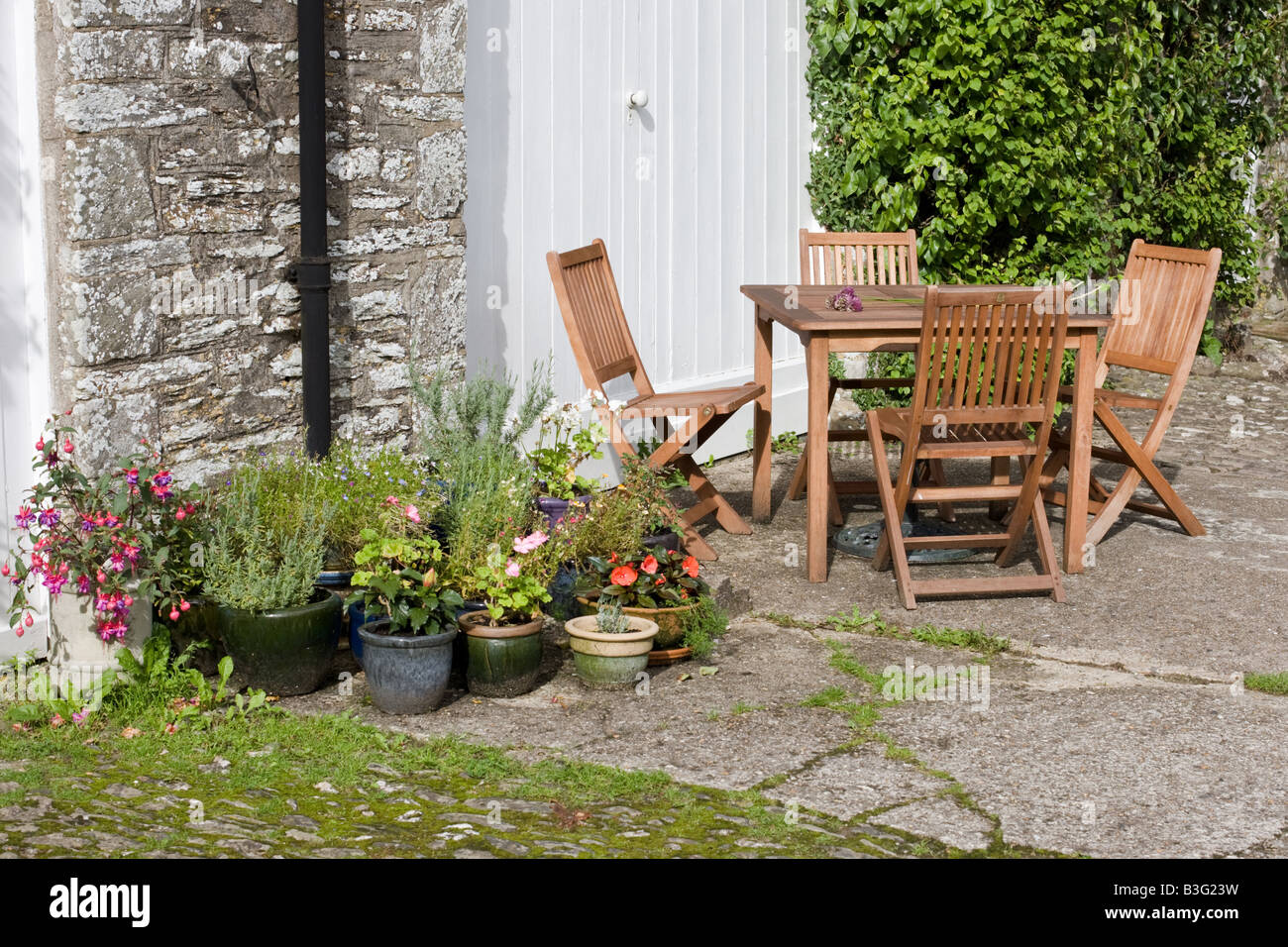 Picnic table and chairs outside country cottage - Stock Image