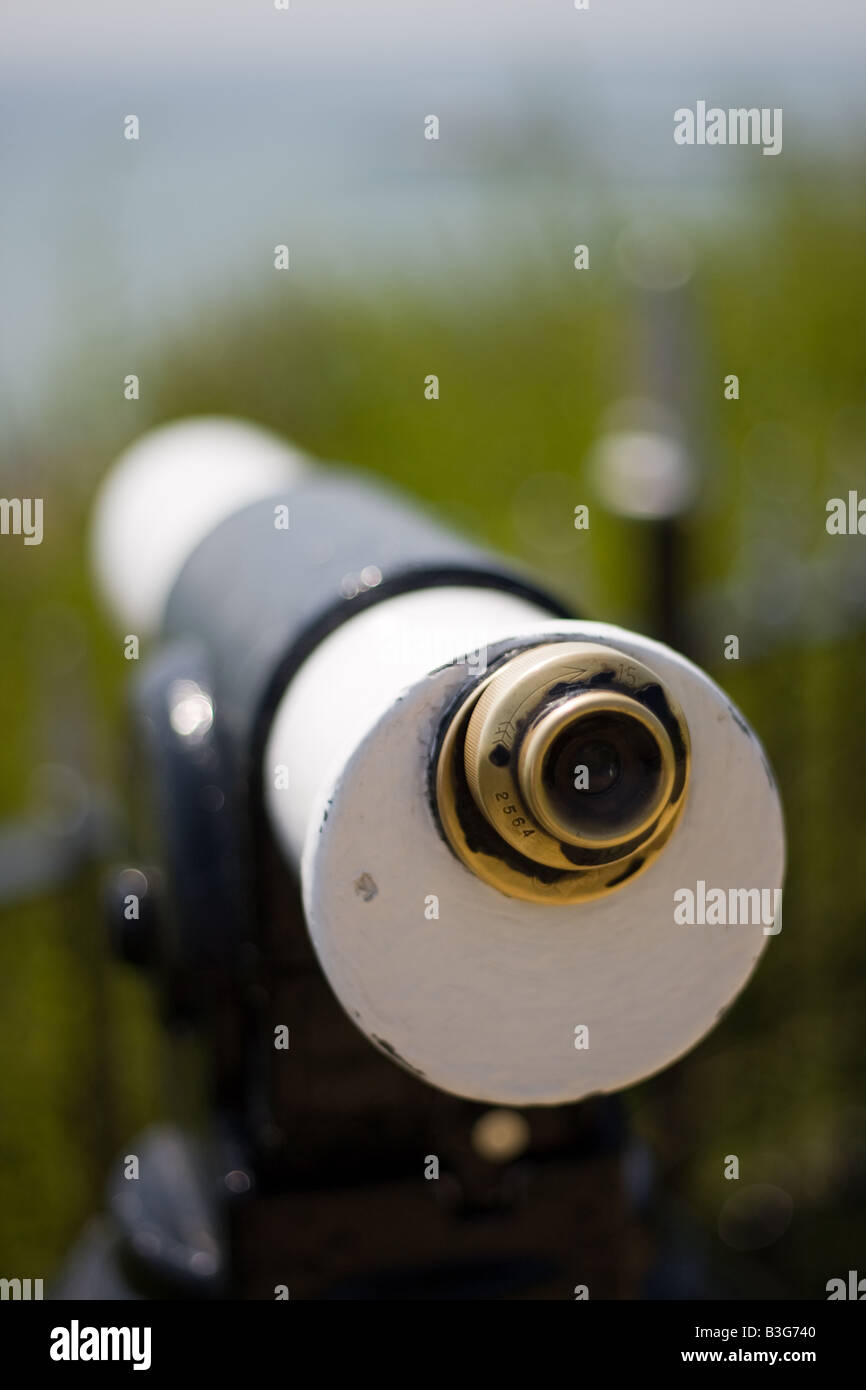 Tourist viewing scope looks out to sea with shallow depth of field - Stock Image