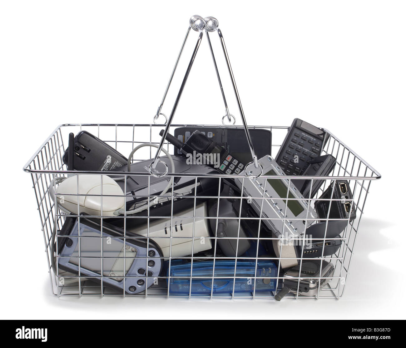 wire Shopping basket with old tech gadgets - Stock Image