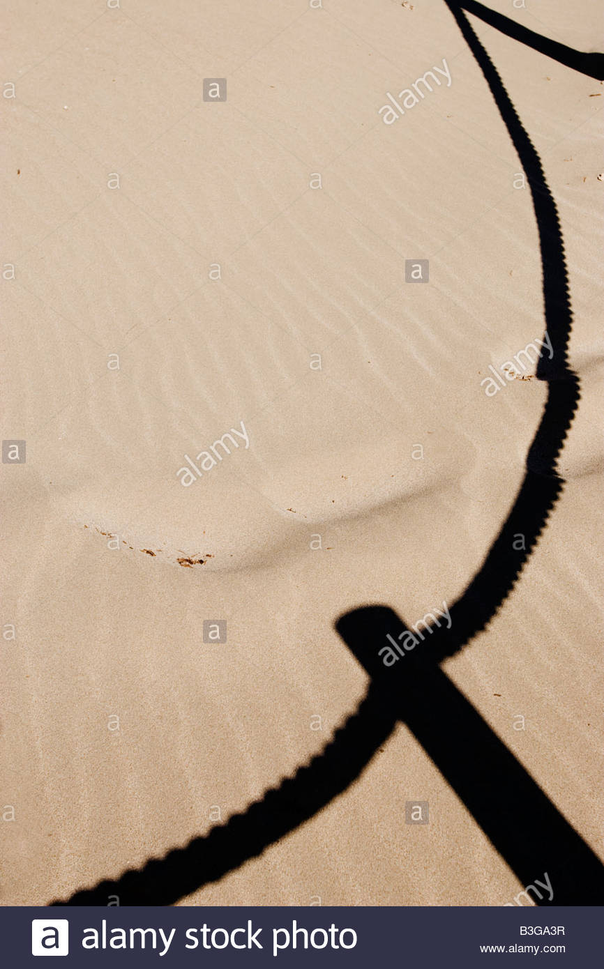 Fence shadow on the sand in the beach - Stock Image