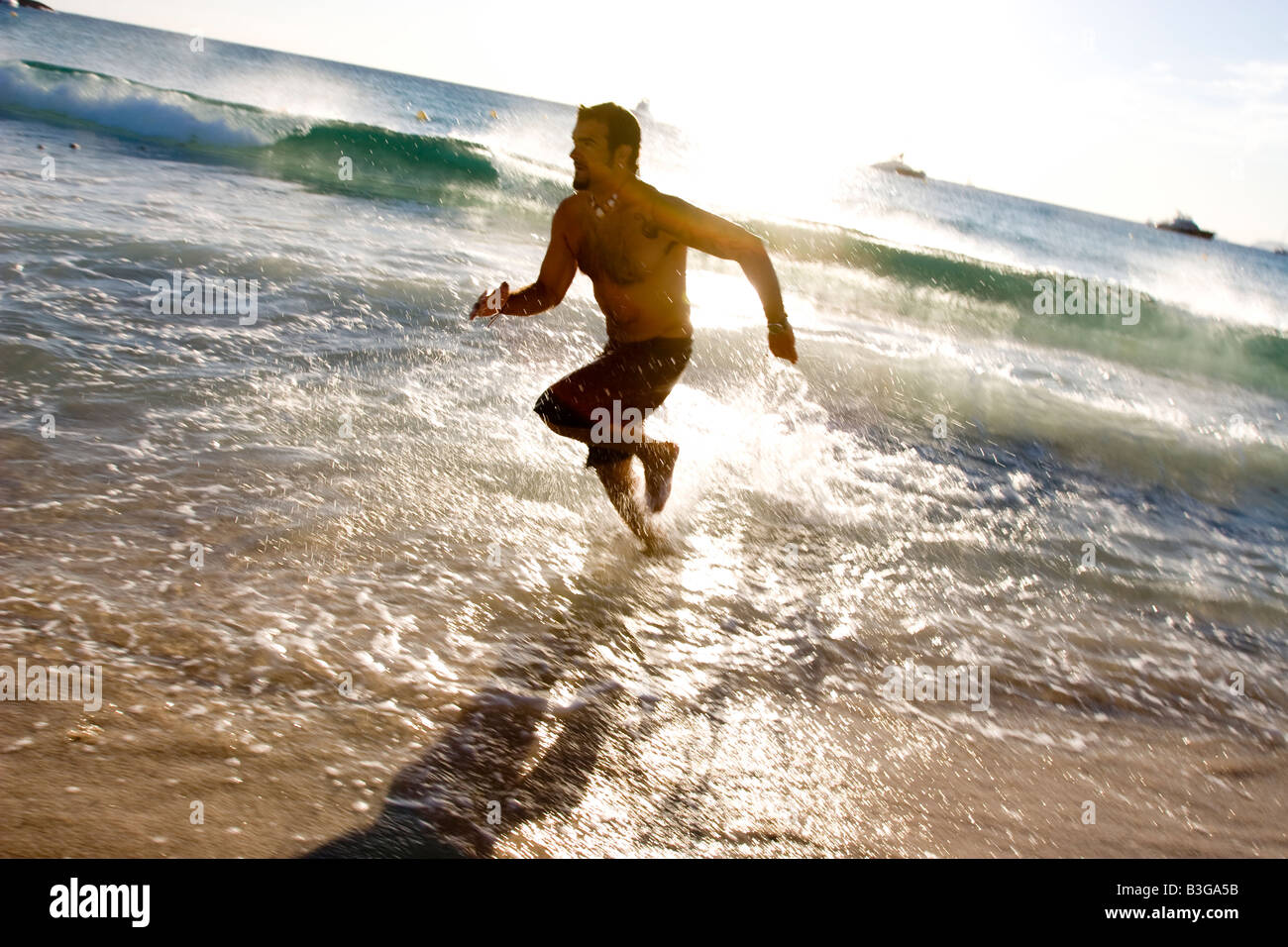 Man running on the beach - Stock Image