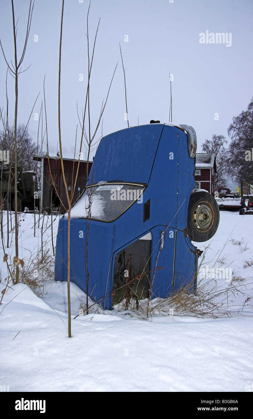 Wrecked blue Saab on its nose in the snow - Stock Image